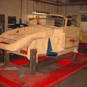 Beispiel: Restauration eines 356/T6 Cabrio-Karosserie. Ohne Außenverkleidung auf der Rahmenlehre. Grundaufbau/Restaurationsabschnitt - fixieren der Achsaufnahmepunkte, Einbau der tragenden Teile wie Bodenbleche, Längsträger, Diagonalverstrebung, Batteriekasten etc. Alle Karosserieteile werden nach original Karosserieplänen und Werkmaßen eingebaut und verschweißt, nur so kann eine optimale Maßhaltigkeit und Statik der Karosserie gewährleistet werden.